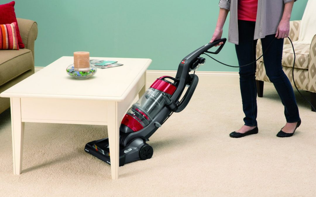 A woman uses a Bissell pet vacuum in her living room