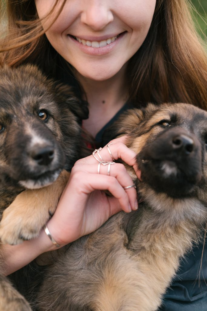 Woman Holding German Shepherd Puppies